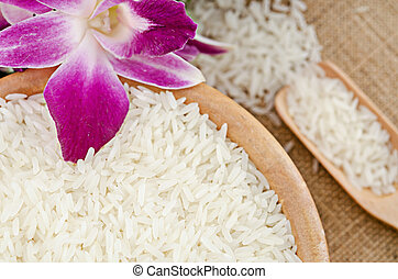 Raw white rice in wooden bowl.
