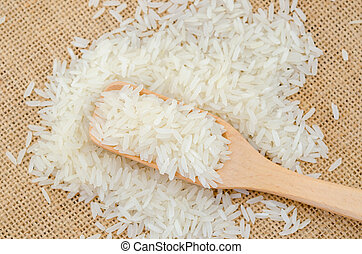 Raw white rice in wooden spoonl.
