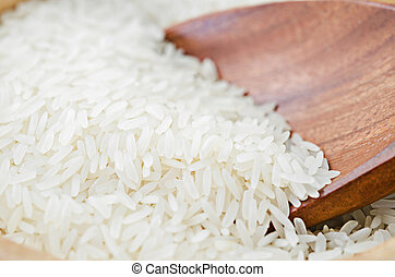 Raw white rice on wooden ladle.