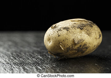raw young potatoes on a black background - raw young...
