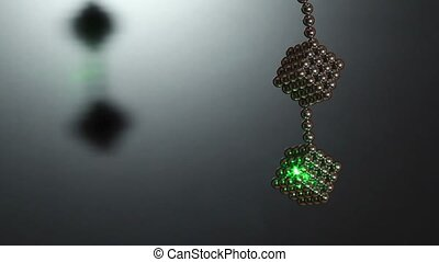 Ray of laser light on cube compound of magnet spheres, which hangs on chain