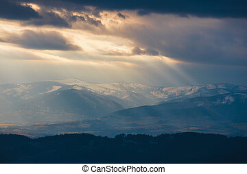 Rays of light pass through the clouds, mountain landscape