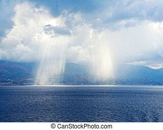 rays of sun breaking through clouds in sea