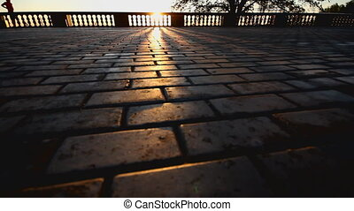 rays of sun over parapet on tile sidewalk