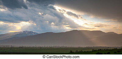 Rays of the sun shining through dark clouds