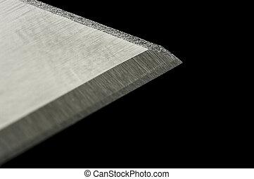 Razor blade macro over black with shallow DOF