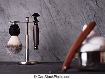 Razor, brush, and perfume on a wooden background.