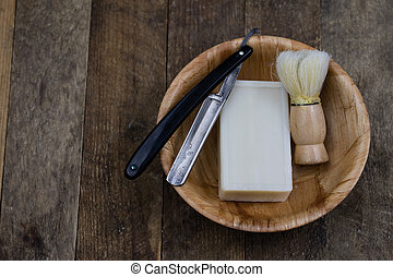 Razor, brush and soap on an old wooden table. Accessories for daily hygiene for men.