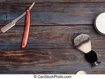 Razor, brush, balsam, perfume on wooden background.