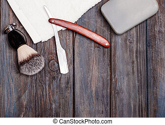 Razor, brush, perfume, towels on a wooden background.