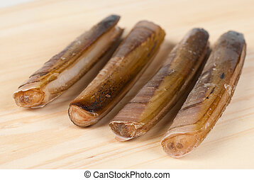 Fresh razor clams in their shell on a wooden board
