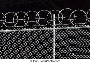 Razor Fence - Razor wire spirals against the dark interior...