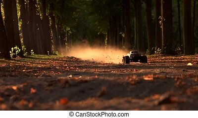 RC car drfting in a forest offroad race. Perspective view of radio controlled monster car drives fast and drifting making dust.