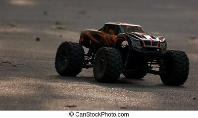 RC monster truck slowly rides backward. Remote control toy car drives back front view.