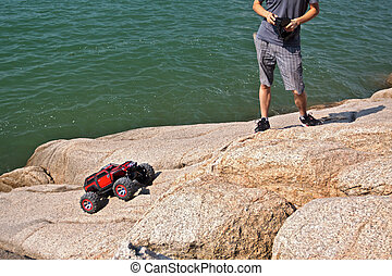 RC toy car on a stone terrain on sea background