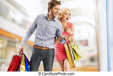 reír, pareja, mirar fijamente, en, el, ventana de la tienda