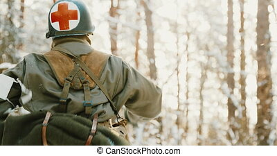Re-enactor Dressed As American Soldier Medic Of USA Infantry Of World War II Fast Running Along Forest Road In Winter Day