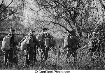Re-enactors Dressed As World War II Russian Soviet Red Army Soldiers Marching Through Forest In Autumn Day. Photo In Black And White Colors. Soldier Of WWII WW2 Times