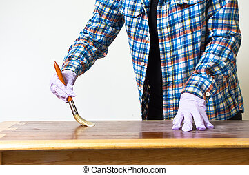Re-finishing a table - Woman sanding and varnishing a table