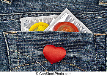 Rea heart and colored condom in blue jeans pocket
