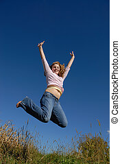 Young female happily jumping in field on a hill with the sky as background
