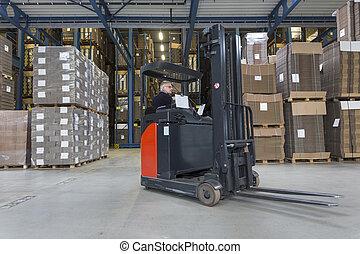 Reach Truck - Reach truck driving around cardboard boxes in...