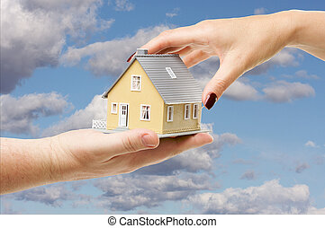 Reaching For A Home - Female hand reaching for a house on a...
