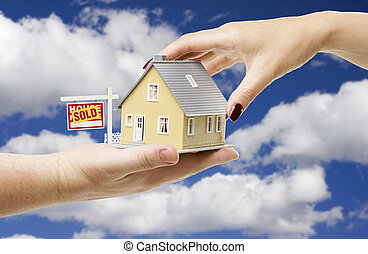 Reaching For A Home with Sold Real Estate Sign on a Bright...