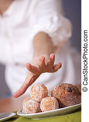 reaching for cakes - female hand reaches for cakes on the...