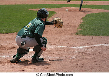 Reaching for the Ball - A catcher coming out his crouch to...