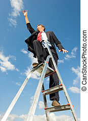 Reaching for the sky - A businessman on a ladder reaching...