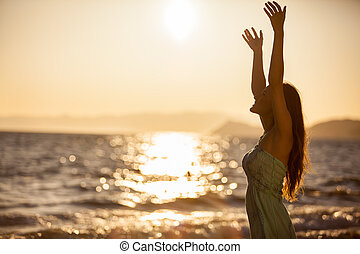 Reaching for the sun - Happy young woman reaching for the...