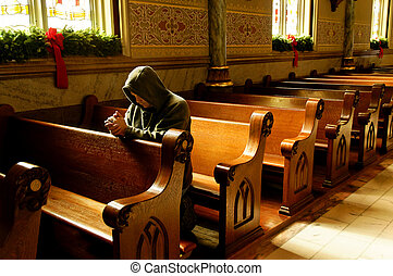 Reaching Out at Christmas - A man kneeling and praying at a...
