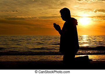 Reaching Out to God - A man kneeling on the beach and...