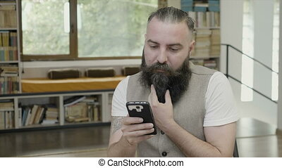 Reaction of a young man with beard reading something on his...