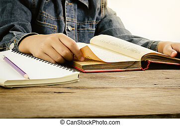 Read a book on a wooden table - Focus hand.