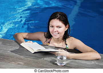 Reading a book - An attractive young woman wearing a bikini...