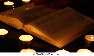 Reading a book by candles.
