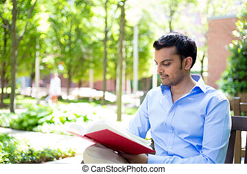 Reading a book outside - Closeup portrait young business man...