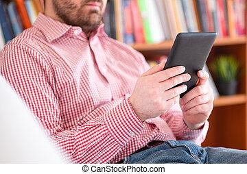 Reading a novel bestseller on ebook reader at home