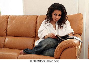 Teenage girl reading a magazine on a sofa