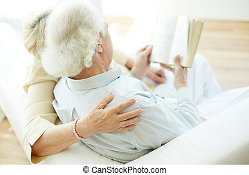 Reading at leisure - Grey-haired elderly man and his wife...