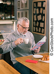 Bearded mature man wearing glasses reading book sitting in bakery