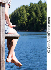 reading book on the cottage dock