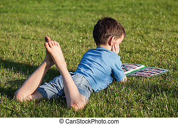 Reading child - A child reading a newspaper on a sunny day