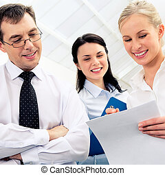 Reading document - Photo of smart woman holding paper in ...