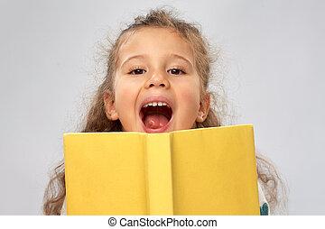 happy little girl hiding behind yellow book