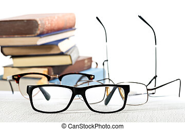 reading glasses and books on the white table