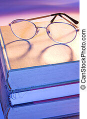 Reading Glasses on books photographed with orange and blue ...