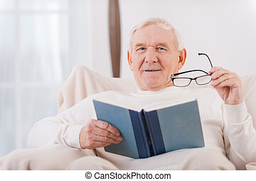 Reading his favorite book . Cheerful senior man reading a book while sitting in chair